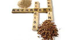 """Buchstaben, die in Scrabble-Manier gelegt wurden und die Worte """"Nährwert"""", """"Eiweiss"""" sowie """"Pektin"""" bilden. Drumherum sid kleine Häufchen Pferdefutter drapiert."""